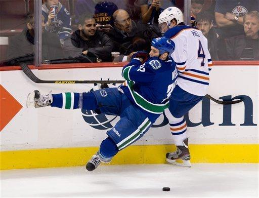 Edmonton Oilers' Taylor Hall, right, trips Vancouver Canucks' Dale Weise and receives a penalty during the third period of an NHL hockey game in Vancouver, British Columbia, on Sunday, Jan. 20, 2013. (AP Photo/The Canadian Press, Darryl Dyck)
