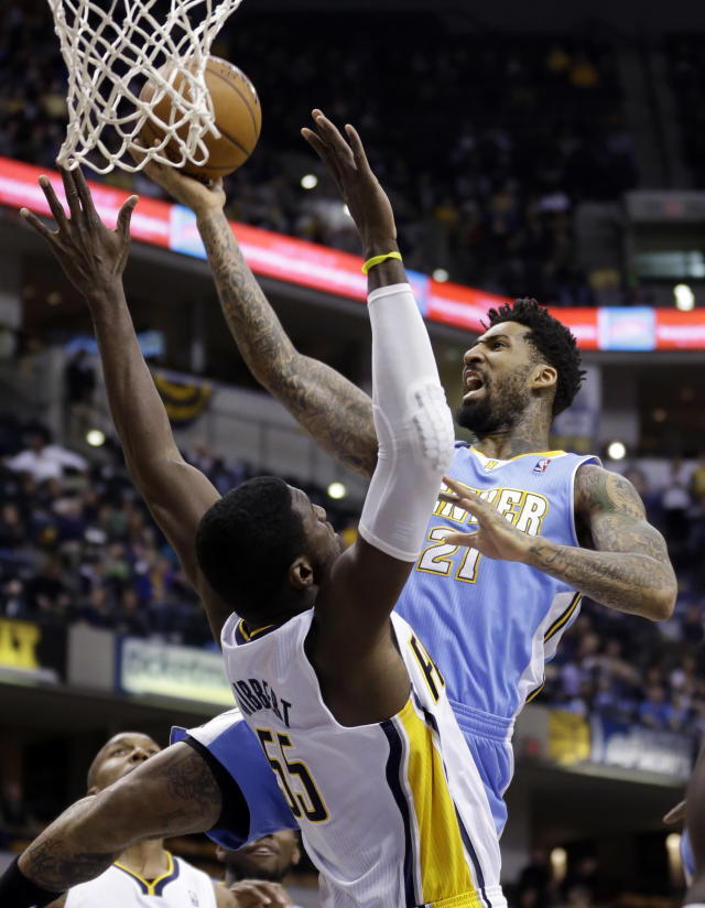 Denver Nuggets forward Wilson Chandler, right, gets a basket over Indiana Pacers center Roy Hibbert in the first half of an NBA basketball game in Indianapolis, Monday, Feb. 10, 2014. (AP Photo/Michael Conroy)