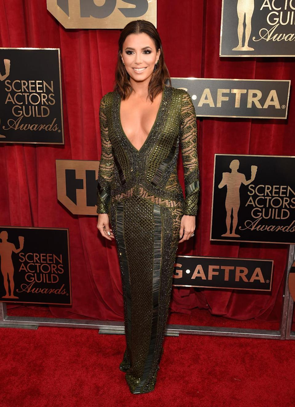 """<p>Eva Longoria channeled Jennifer Lopez on the red carpet in a revealing Julien MacDonald dress. The military green gown plunged in the front — and did the same in the back. She assumed that the designer's inspiration for the stunning design and her overall look for the night was to """"show some skin,"""" and the <i>Telenovela </i>star was probably right. <i>Photo: Getty Images</i></p>"""