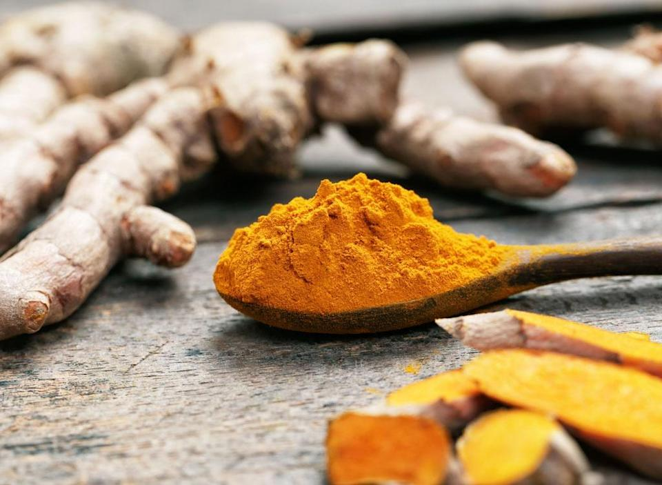 Turmeric powder on wooden spoon