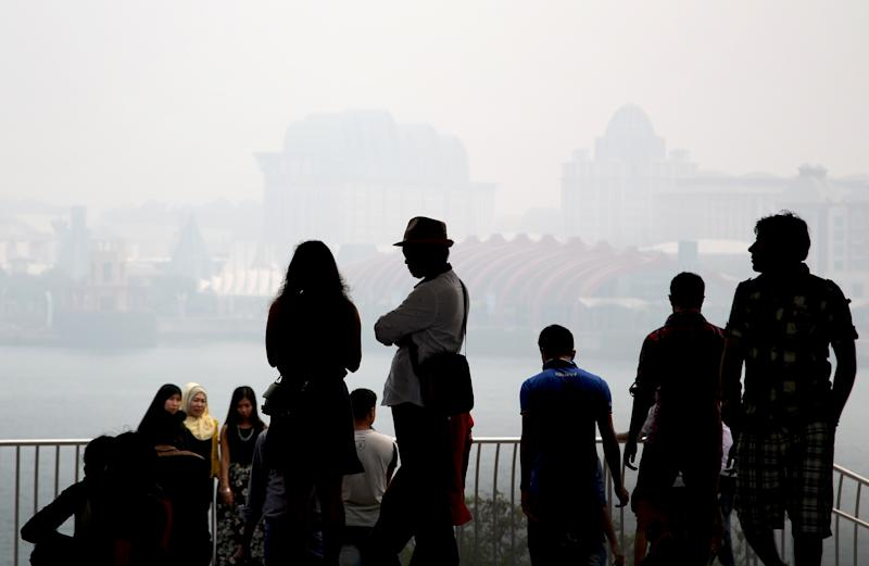Tourists are silhouetted as they view Sentosa against the backdrop of the haze in 2015. (AP file photo)