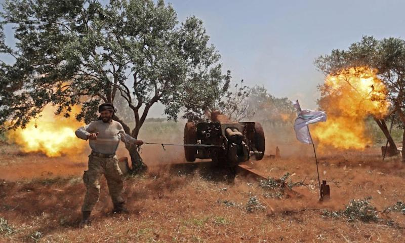A National Liberation Front fighter in Idlib fires a heavy artillery gun against regime positions