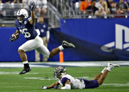 "Penn State running back <a class=""link rapid-noclick-resp"" href=""/ncaaf/players/256698/"" data-ylk=""slk:Saquon Barkley"">Saquon Barkley</a> (26) leaps over Washington defensive back <a class=""link rapid-noclick-resp"" href=""/ncaaf/players/268148/"" data-ylk=""slk:Myles Bryant"">Myles Bryant</a> (5) during the second half of the Fiesta Bowl NCAA college football game Saturday, Dec. 30, 2017, in Glendale, Ariz. (AP Photo/Ross D. Franklin)"