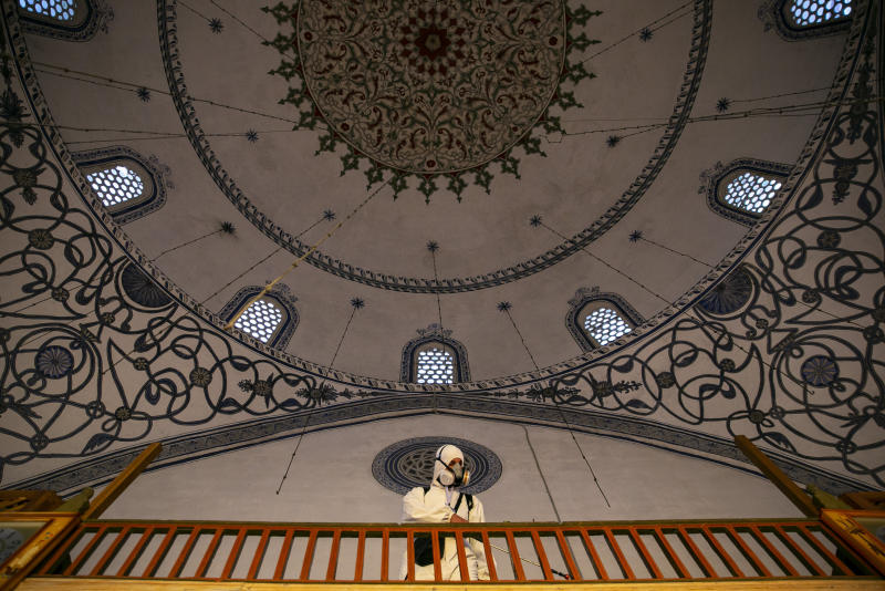 Disinfection team disinfect the premises of the grand mosque in capital Pristina, Kosovo on Thursday, May 28, 2020. Kosovo's mosques reopened on Thursday after more than two months of the virus lockdown. (AP Photo/Visar Kryeziu)