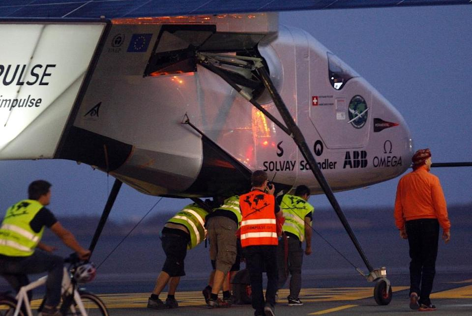 Members of the Solar Impulse 2 team escort the solar-powered plane before its take off from Muscat airport in Oman early on March 10, 2015 (AFP Photo/Mohammed Mahjoub)