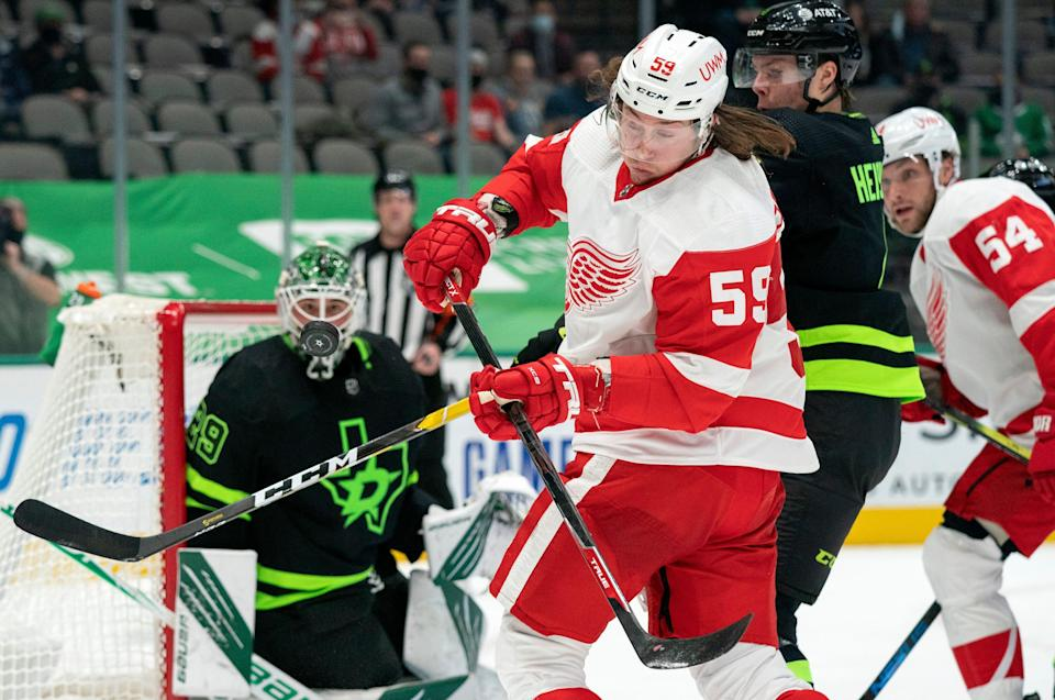 Detroit Red Wings left wing Tyler Bertuzzi (59) tries to control the puck as Dallas Stars defenseman Miro Heiskanen, right, and goaltender Jake Oettinger (29) watch during the first period of an NHL hockey game Thursday, Jan. 28, 2021, in Dallas.