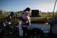 A woman carries a baby amid her belongings and destroyed shack as police evict people from a squatters camp in Guernica, Buenos Aires province, Argentina, Thursday, Oct. 29, 2020. A court ordered the eviction of families who are squatting here since July, but the families say they have nowhere to go amid the COVID-19 pandemic. (AP Photo/Natacha Pisarenko)