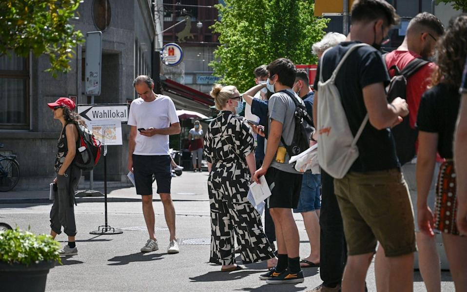 People queue at a ballot station in Basel, Switzerland, as the country votes on topics including Covid-19 laws, on June 13 2021 - Fabrice Coffrini/AFP