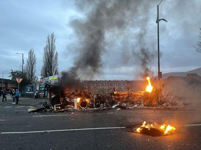 The wreckage of a Translink Metrobus on fire on the Shankill Road in Belfast