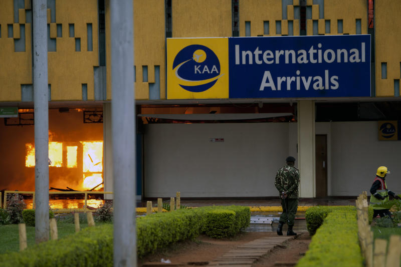 A policeman stands guard as a fire engulfs the arrivals hall of the Jomo Kenyatta International Airport in Nairobi, Kenya Wednesday, Aug. 7, 2013. The Kenya Airports Authority said the Kenya's main international airport has been closed until further notice so that emergency teams can battle the fire. (AP Photo/Sayyid Azim)