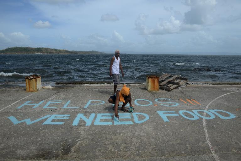 "A man paints a message on a baskeball court that reads ""Help SOS We Need Food"" at Anibong in Tacloban, the Philippines on November 11, 2013"