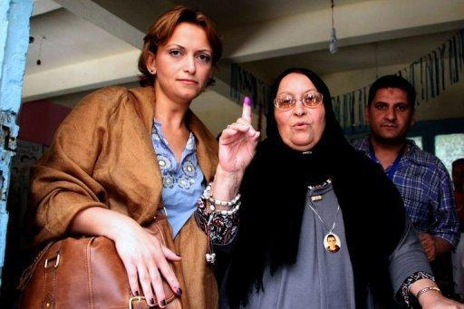 Layla Marzuq (C), the mother of Egyptian youth Khaled Said who died following police questioning before the Egyptian uprising, shows her ink-stained finger as she walks out of a polling station