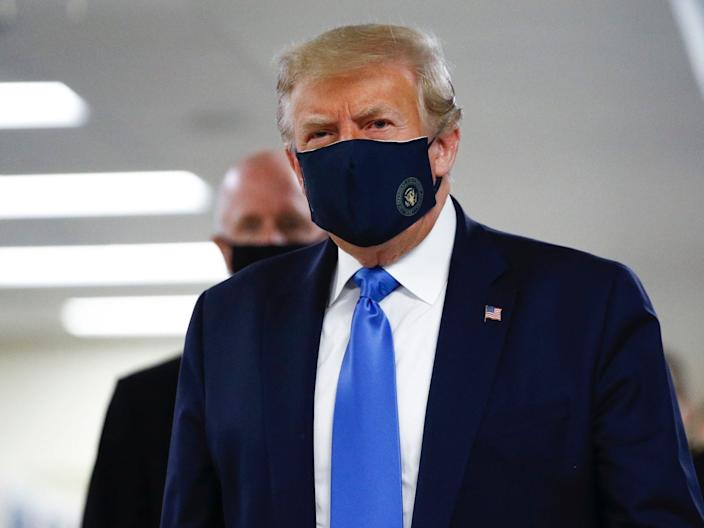 President Donald Trump wears a mask as he walks down the hallway during his visit to Walter Reed National Military Medical Center in Bethesda, Md., Saturday, July 11, 2020.