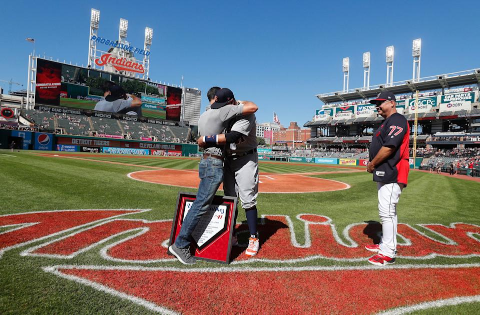 Indians president Chris Antonetti, left, embraces Tigers designated hitter Victor Martinez after presenting him with a plaque as Indians manager Terry Francona looks on before the start of the game against the Tigers on Saturday, Sept.15, 2018, in Cleveland.