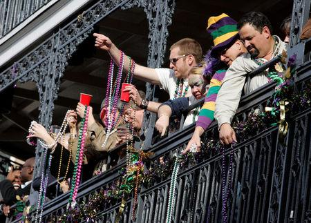 FILE PHOTO: Revelers throw beads from a balcony while celebrating Lundi Gras on Bourbon Street in the French Quarter of New Orleans, Louisiana, U.S., February 19, 2007. REUTERS/Sean Gardner/File Photo