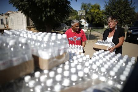 Donna Johnson, 70, (R) lifts pallets of donated bottled water from the back of her truck during her daily delivery run to residents whose wells have run dry, with resident Ruben Perez, 68, in Porterville, California October 14, 2014. REUTERS/Lucy Nicholson