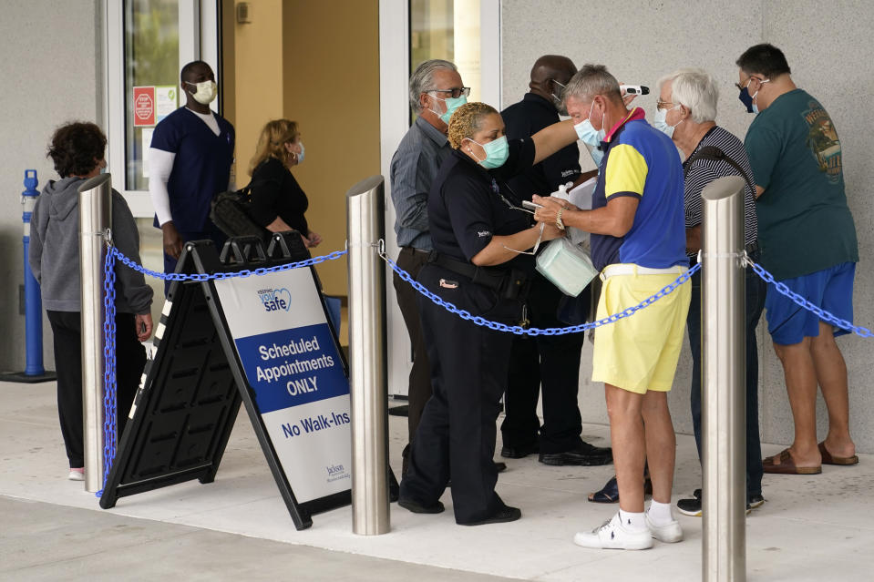 FILE - In this Jan. 27, 2021, file photo, people wait in line to receive the Pfizer-BioNTech COVID-19 vaccine at the Jackson Hospital in Miami. The Associated Press was given exclusive access to a recent day of vaccinations at Jackson Memorial hospital system. (AP Photo/Lynne Sladky, File)