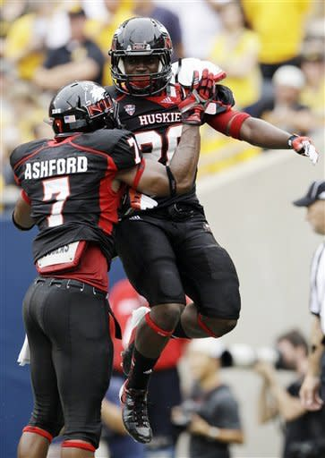 Northern Illinois running back Keith Harris, Jr. (20) celebrates with wide receiver Perez Ashford (7) after scoring a touchdown during the first half of an NCAA college football game against Iowa at Soldier Field in Chicago, Saturday, Sept. 1, 2012. (AP Photo/Nam Y. Huh)