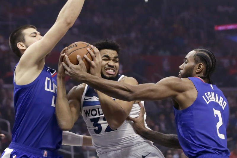 Minnesota Timberwolves center Karl-Anthony Towns (32) collides with Los Angeles Clippers center Ivica Zubac (40) with forward Kawhi Leonard (2) defending during the first half of an NBA basketball game in Los Angeles, Saturday, Feb. 1, 2020. (AP Photo/Alex Gallardo)