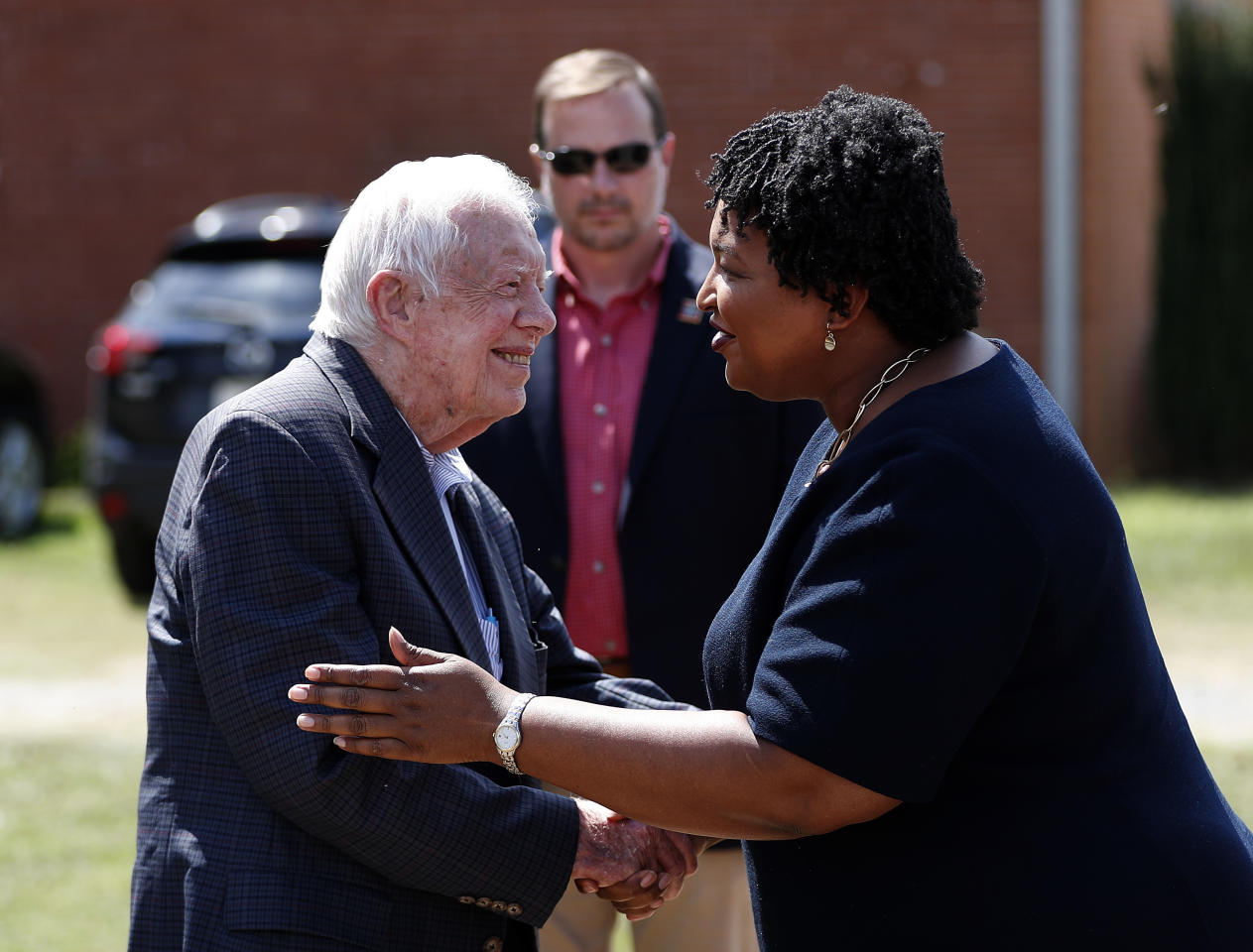 Former President Jimmy Carter greets Democratic gubernatorial candidate Stacey Abrams as she arrives for during a news conference to announce her rural health care plan Tuesday, Sept. 18, 2018, in Plains, Ga. (AP Photo/John Bazemore)