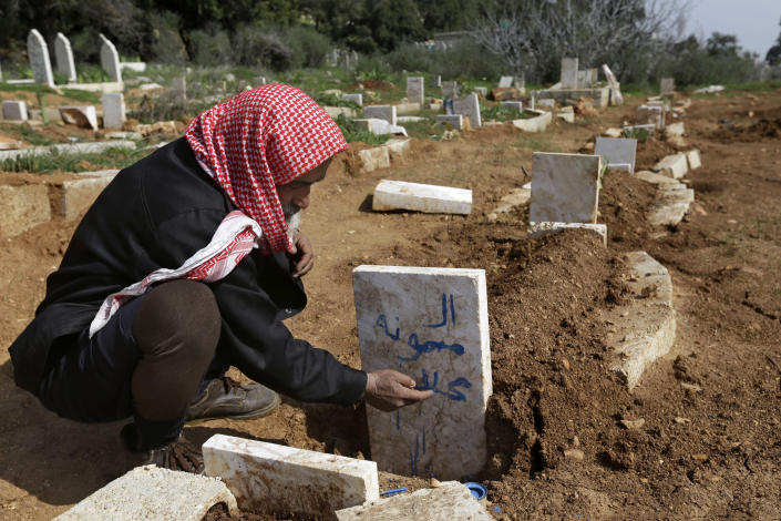 A Syrian villager, Abu Ibrahim, 73, writes the name of his granddaughter on her grave who was killed from an airstrike by Syrian government forces, at Jabal al-Zaweya village of Sarja, in Idlib, Syria, Sunday, Feb. 24, 2013. Syrian rebels used captured tanks to launch a fresh offensive on a government complex housing a police academy near Aleppo and clashed with government troops protecting the strategic installation on Sunday. (AP Photo/Hussein Malla)