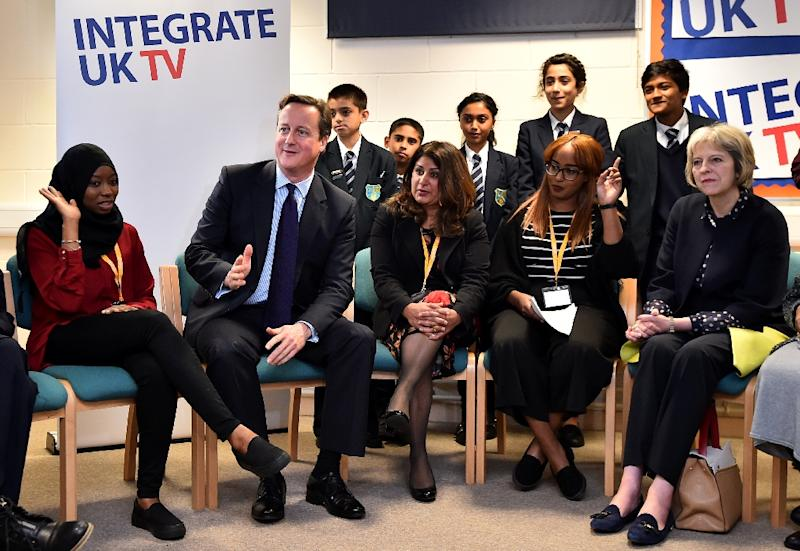 British Prime Minister David Cameron (2L) and Home Secretary Theresa May (R) speak with schoolchildren on a visit to Luton, north of London, on October 19, 2015 to announce a new government strategy for tackling extremism (AFP Photo/Ben Stansall)