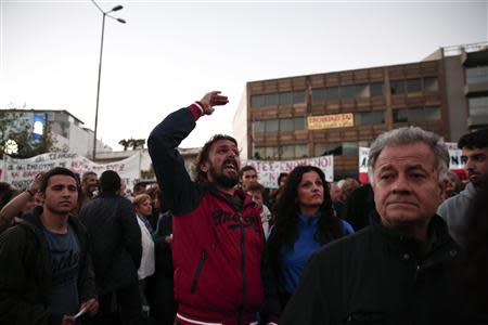 Protester yells at policemen during a rally outside former state television ERT headquarters at Agia Paraskevi suburb north of Athens