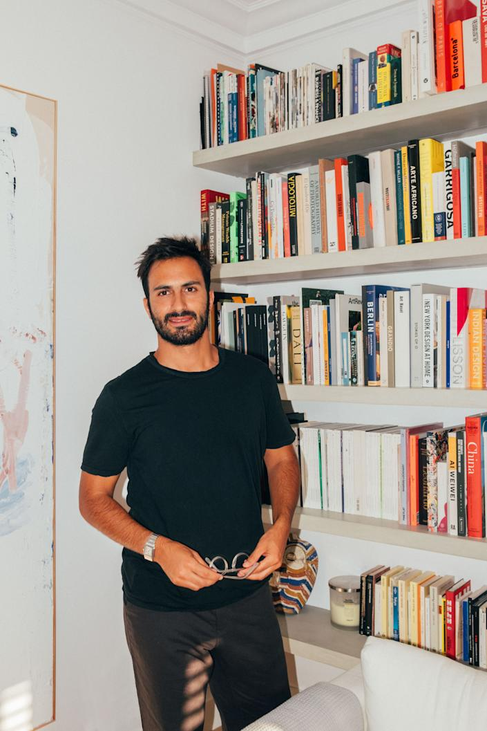 "<div class=""caption""> Juan in his natural habitat, surrounded by art and books. </div>"