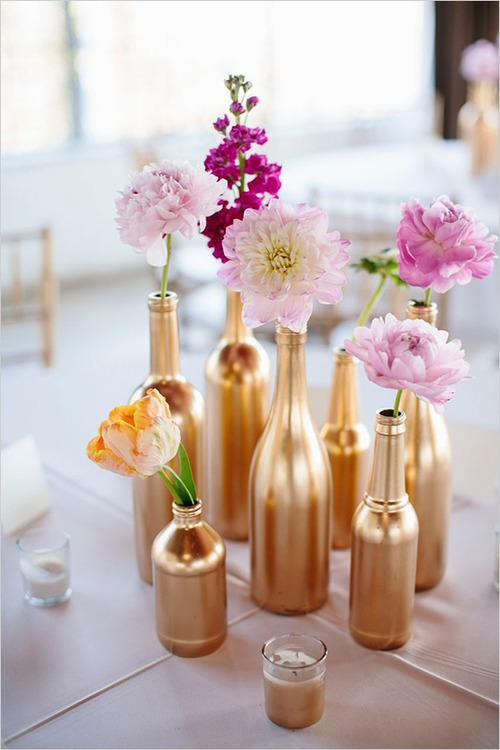 flowers styled in gold painted wine bottles