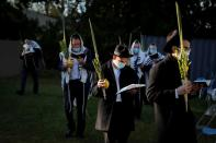 "Orthodox Jews gather for ""Hoshanot prayers"" as part of their Sukkot observance on neighborhood lawn in Monsey, New York"