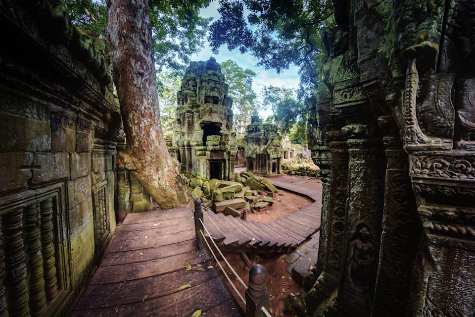 """This famous twelfth-century temple in <a href=""""https://www.cntraveler.com/stories/2016-06-02/the-best-doughnuts-are-in-cambodia?mbid=synd_yahoo_rss"""" rel=""""nofollow noopener"""" target=""""_blank"""" data-ylk=""""slk:Cambodia"""" class=""""link rapid-noclick-resp"""">Cambodia</a> is modeled after the mythological Mount Meru, where Hindus believe the ancient gods live. At its highest point, Angkor Wat reaches more than 700 feet tall. The temple complex, which has ties to both Hinduism and Buddhism, has walls covered with carvings, including over 3,000 <em>asparas</em> (nymphs) and many other mythological events and figures. It's a vastly popular tourist attraction: in 2018, short of 3 million tourists paid a visit, which was a third of all who stepped foot in Cambodia. Tourists begin lining <a href=""""https://www.cntraveler.com/stories/2016-03-10/the-secret-to-having-angkor-wat-all-to-yourself?mbid=synd_yahoo_rss"""" rel=""""nofollow noopener"""" target=""""_blank"""" data-ylk=""""slk:up as early as 4:30 a.m."""" class=""""link rapid-noclick-resp"""">up as early as 4:30 a.m.</a> for tickets, so make sure you get there early—or be prepared to wait."""