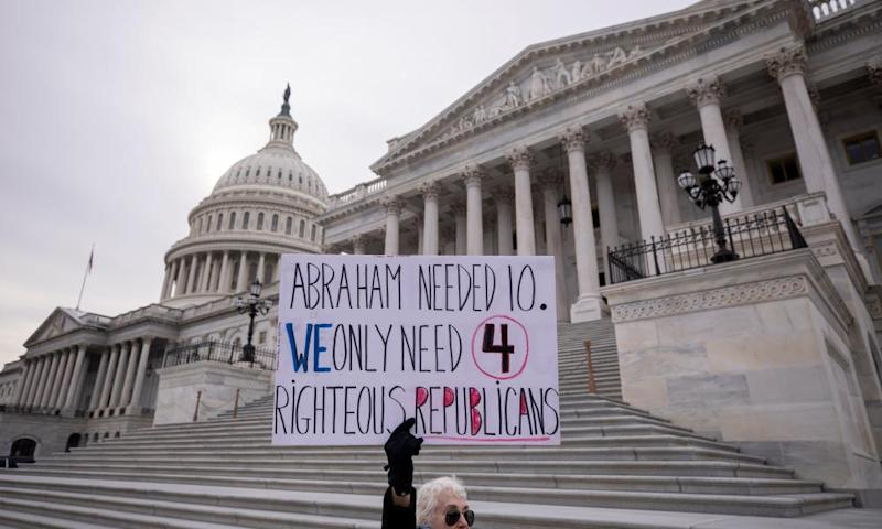 A protester holds a sign outside the impeachment trial on Thursday.