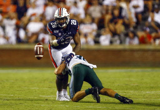 Auburn running back JaTarvious Whitlow (28) fumbles the ball as he is tackled by Tulane safety Tirise Barge (33) during the second half of an NCAA college football game Saturday, Sept. 7, 2019, in Auburn, Ala. (AP Photo/Butch Dill)