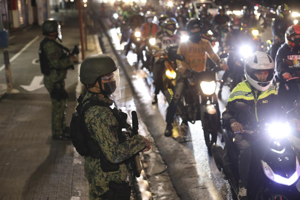 Police officers inspect motorcycle riders at a checkpoint during a stricter lockdown as a precaution against the spread of the coronavirus at the outskirts of Marikina City, Philippines on Friday, August 6, 2021. Thousands of people jammed coronavirus vaccination centers in the Philippine capital, defying social distancing restrictions, after false news spread that unvaccinated residents would be deprived of cash aid or barred from leaving home during a two-week lockdown that started Friday. (AP Photo/Basilio Sepe)