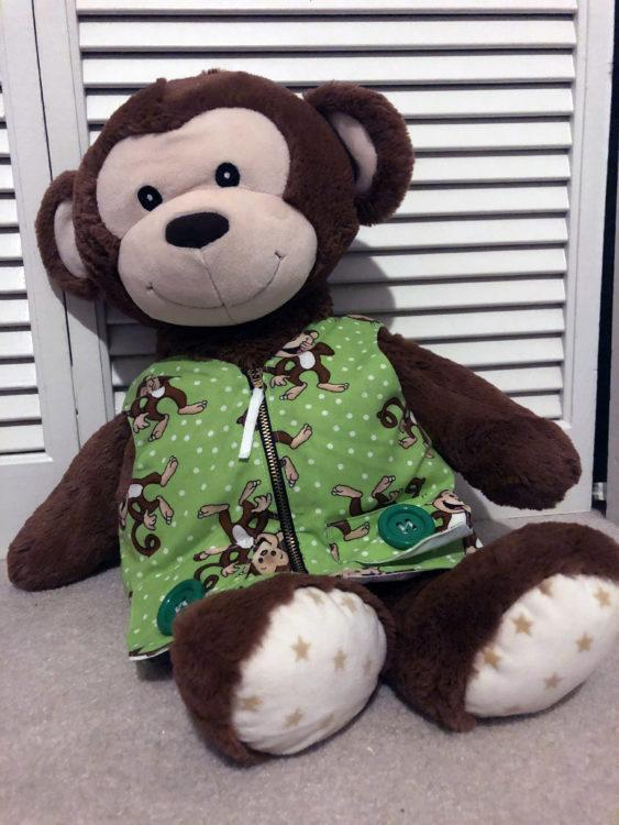 A picture of a big stuffed monkey wearing a green vest.
