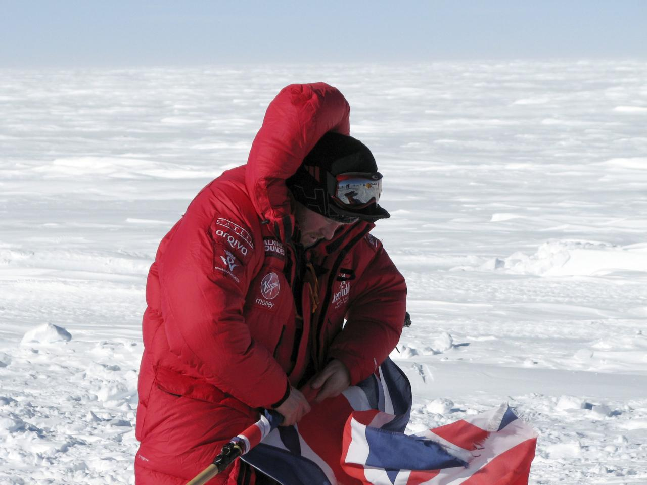 Prince Harry rolls the Union Jack on the first day of the Virgin Money South Pole Allied Challenge 2013 expedition in Antarctica December 1, 2013. Prince Harry set off on Sunday on his 300 kilometre (186 miles) walk to the South Pole for the charity Walking With The Wounded (WWTW) to raise money for wounded servicemen and women. The Virgin Money South Pole Allied Challenge 2013, of which Harry is patron, will see the participants race across three degrees to the South Pole. All 12 injured service personnel from Britain, America, Canada and Australia have overcome life-changing injuries and undertaken challenging training programmes to prepare themselves for the conditions they will face in Antarctica. Trekking around up to 20km (12 miles) per day, the teams will endure temperatures as low as minus 45 centigrades (minus 113 Fahrenheit) and 80 kph (50 mph) winds as they pull their 70 kg (154 pound) sleds, known as pulks, towards the southernmost point on the globe. Picture taken December 1, 2013. REUTERS/Victoria Nicholson/Walking With the Wounded (ANTARCTICA - Tags: ENVIRONMENT ROYALS SPORT MILITARY) NO COMMERCIAL OR BOOK SALES. NO SALES. FOR EDITORIAL USE ONLY. NOT FOR SALE FOR MARKETING OR ADVERTISING CAMPAIGNS. MANDATORY CREDIT