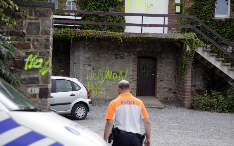 FILE - In this Aug. 1, 2012 file photo, a police officer walks by graffiti sprayed onto the entrance of the Poor Clares Monastery in Malonne, Belgium. Graffiti was sprayed in reaction to the eventual arrival to the monastery of Michelle Martin, the ex-wife of Belgium's child killer Marc Dutroux - the man responsible for several rapes and deaths in the 1990's. A court ruled in favor of freeing Michelle Martin to live in the monastery. Martin, is halfway through a 30-year jail sentence she received for complicity in the Dutroux case. Graffiti reads in French 'No' and includes the initials M.M. for Michelle Martin. (AP Photo/Virginia Mayo, File)