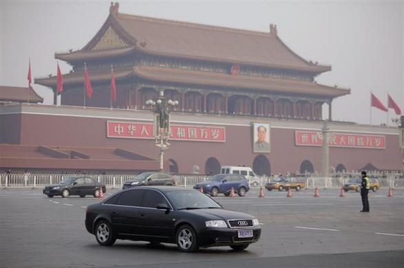 An Audi car drives past Tiananmen Square as a police officer stands guard on a street in central Beijing February 29, 2012.