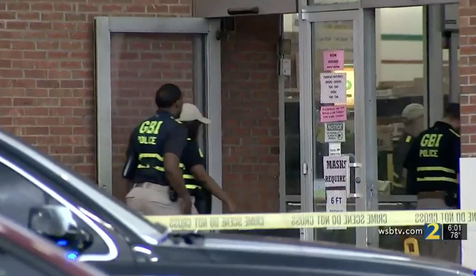 Police enter the store after the shooting.