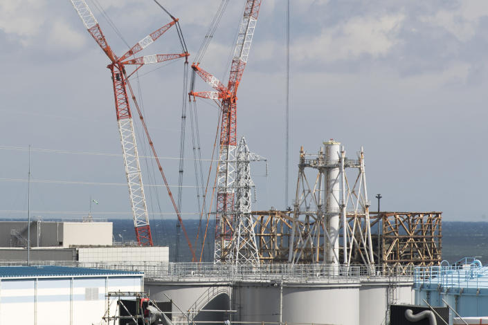 This photo shows the damaged Unit 1 reactor, back, and part of the exhaust stack shared with the Unit 1 and 2 reactors at the Fukushima Daiichi nuclear power plant in Okuma town, Fukushima prefecture, northeastern Japan, Saturday, Feb. 27, 2021. The exhaust stack has gotten its upper half cut off due to safety concerns. (AP Photo/Hiro Komae)