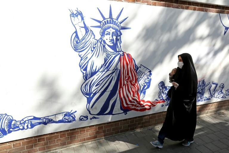 An Iranian woman walks past a mural painted on the outer walls of the former US embassy in the capital Tehran on September 20, 2020