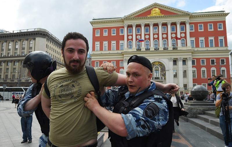 Russian riot policemen detain Orthodox activist Dmitry Enteo during an unauthorized rally in central Moscow on May 30, 2015