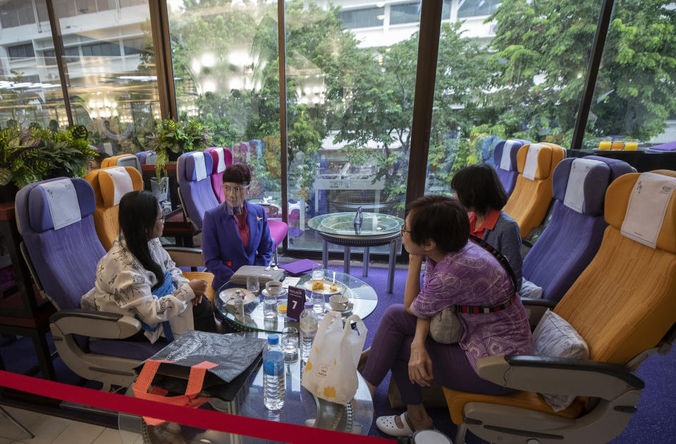 A flight attendant talks to customers after serving meals in a flight-themed restaurant at the Thai Airways head office in Bangkok, Thailand on Oct. 3, 2020. The airline is selling time on its flight simulators to wannabe pilots while its catering division is serving meals in a flight-themed restaurant complete with airline seats and attentive cabin crew. The airline is trying to boost staff morale, polish its image and bring in a few pennies, even as it juggles preparing to resume international flights while devising a business reorganization plan. (AP Photo/Sakchai Lalit)