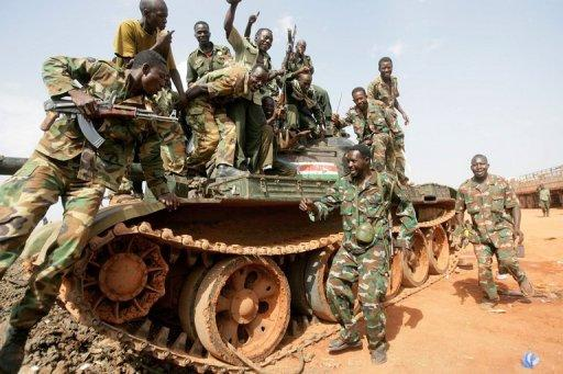 Sudanese soldiers pose on a seized tank in the oil region of Heglig in April 2012