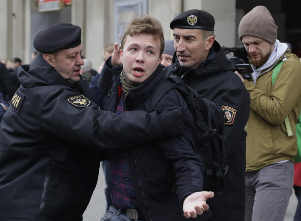 FILE - In this Sunday, March 26, 2017 file photo, Belarus police detain journalist Raman Pratasevich, center, in Minsk, Belarus. Raman Pratasevich, a founder of a messaging app channel that has been a key information conduit for opponents of Belarus' authoritarian president, has been arrested after an airliner in which he was riding was diverted to Belarus because of a bomb threat. The presidential press service said President Alexander Lukashenko personally ordered that a MiG-29 fighter jet accompany the Ryanair plane — traveling from Athens, Greece, to Vilnius, Lithuania — to the Minsk airport. (AP Photo/Sergei Grits, File)