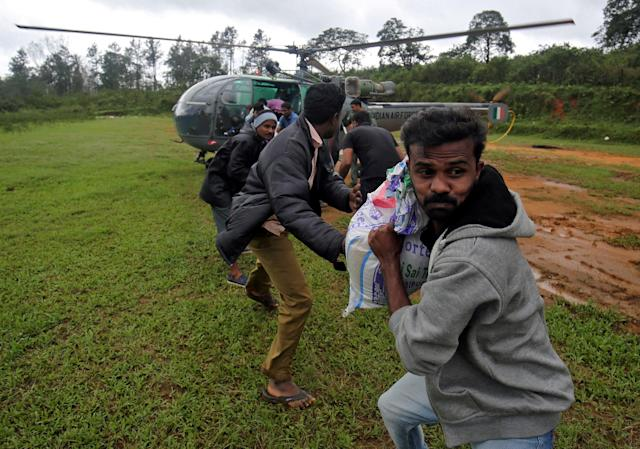 <p>Flood victims unload food and relief material from an Indian Air force helicopter at Nelliyampathy Village, in the southern state of Kerala, India. (Reuters) </p>