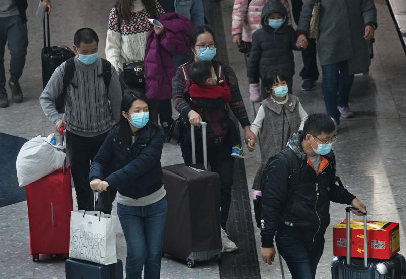 Passengers wear protective face masks arrive at the high speed train station in Hong Kong, Tuesday, Jan. 28, 2020. Hong Kong's leader has announced that all rail links to mainland China will be cut starting Friday as fears grow about the spread of a new virus. (AP Photo/Vincent Yu)