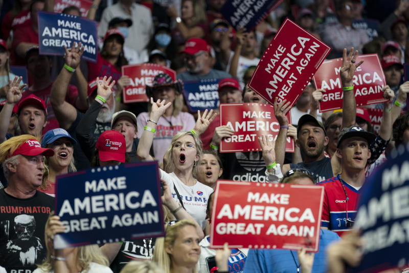Supporters of President Donald Trump cheer as Vice President Mike Pence speaks during a campaign rally at the BOK Center, Saturday, June 20, 2020, in Tulsa, Okla. Trump is asking Americans to let him keep his job. His critics are asking how much of that job he's actually doing. Those questions have gotten louder in recent days following revelations that Trump didn't read at least two written intelligence briefings detailing concerns that Russia was paying bounties to the Taliban for the deaths of Americans in Afghanistan. (AP Photo/Evan Vucci)