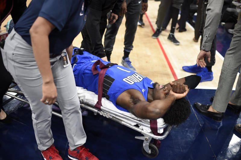 Orlando Magic forward Jonathan Isaac is taken off the court on a stretcher after he sustained an injury during the first half of the team's NBA basketball game against the Washington Wizards, Wednesday, Jan. 1, 2020, in Washington. (AP Photo/Nick Wass)