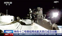 In this image taken from video footage run by China's CCTV, astronaut Liu Boming steps out of core module of the China's new space station in space on Sunday, July 4, 2021. Two astronauts made the first space walk on Sunday outside China's new orbital station to work on setting up a 15-meter (50-foot) long robotic arm. (CCTV via AP Video)